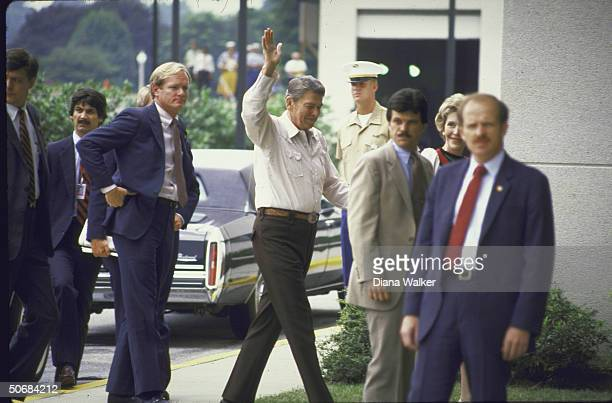 Secret service men surround US Pres Ronald Reagan and his wife as they enter Bethesda Naval Hospital where he will undergo a colon operation