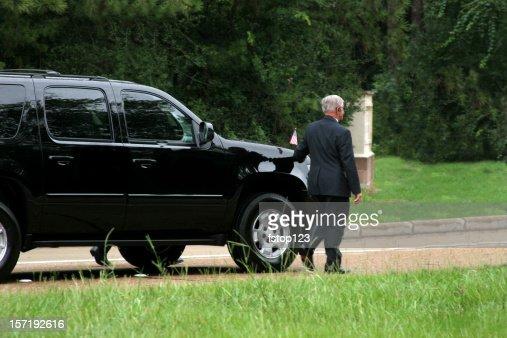 Secret Service men walking beside black SUV. Motorcade.