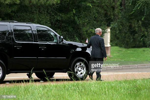 Secret Service men walking beside black SUV. Motorcade.