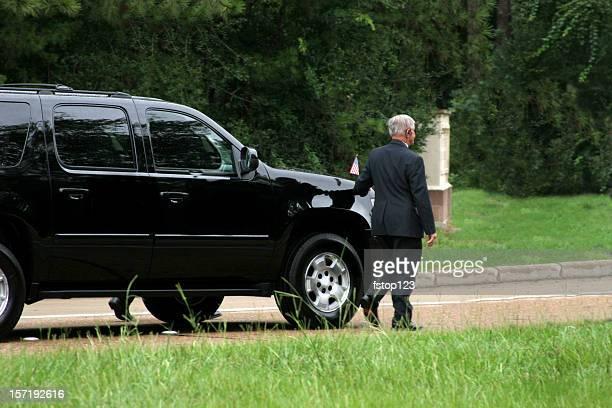 Secret Service men walking Neben schwarz SUV. Fahrzeugkolonne.