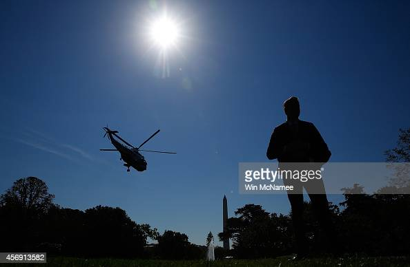 Secret Service officer stands guard in the foreground as Marine One carrying US President Barack Obama departs the White House October 9 2014 in...