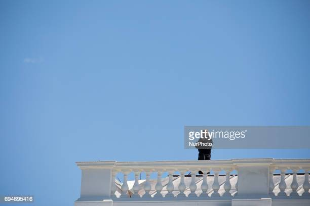 A Secret Service officer stands guard on the roof of the North Portico overlooking the North Lawn of the White House on Friday June 9 2017