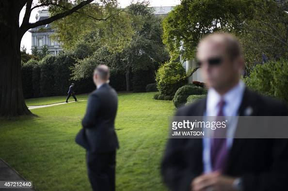US Secret Service officers stand watch as US President Barack Obama returns to the Oval Office at the White House in Washington DC October 14 2014...