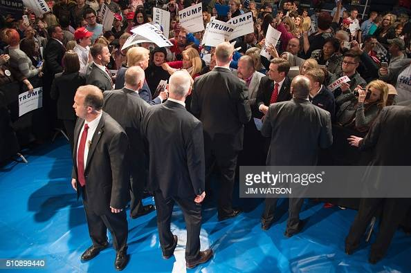 US Secret Service officers surround Republican presidential candidate Donald Trump as he signs autographs for supporters during a campaign rally in...