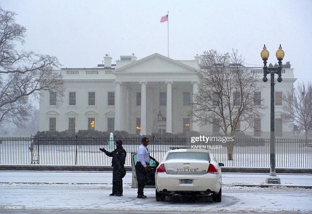 US Secret Service police officers man their posts in front of the White House during a snow strom March 3, 2014 in Washington, DC. Snow began falling in the nation's capital early Monday, and officials warned people to stay off treacherous, icy roads a scene that has become familiar to residents in the Midwest, East and even Deep South this year. Schools were canceled, bus service was halted in places and federal government workers in the DC area were told to stay home Monday. AFP PHOTO / Karen BLEIER