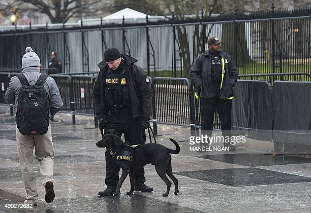 A Secret Service uniformed division dog sniffs at a passerby in front of the White House on November 30 2015 in Washington DC AFP PHOTO/MANDEL NGAN /...