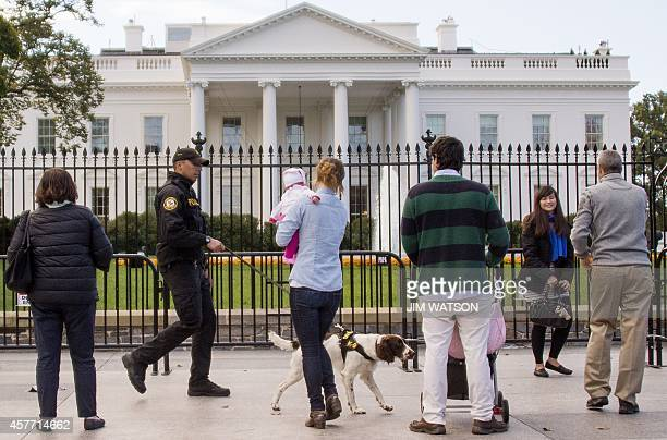 Secret Service Uniformed Division officer and his K9 dog patrol the fence line of the White House in Washington DC October 23 2014 A suspect who...