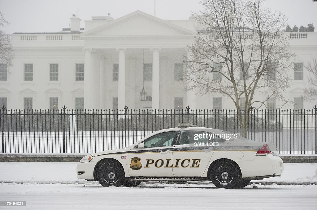 Secret Service Uniformed Division police car is parked in front of the White House and Lafayette Park during a snow storm in Washington, DC, March 3, 2014. Snow began falling in the nation's capital early Monday, and officials warned people to stay off treacherous, icy roads a scene that has become familiar to residents in the Midwest, East and even Deep South this year. Schools were canceled, bus service was halted in places and federal government workers in the DC area were told to stay home Monday. AFP PHOTO / Saul LOEB