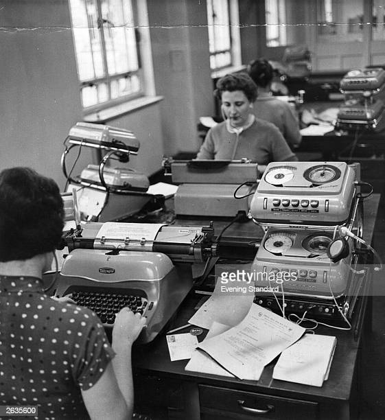 Secretaries type while listening to recording machines in the typing pool