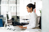 Multi ethnic business woman working with computer at the office. Focused young businesswoman checking email with laptop. Office worker typing on a keyboard in her office.
