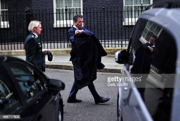 Secretary General Anders Fogh Rasmussen puts on his jacket after giving a press briefing following a meeting with British Prime Minister David...