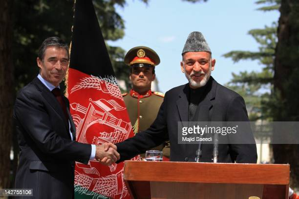 Secretary General Anders Fogh Rasmussen shakes hands with Afghan President Hamid Karzai during a joint press conference at the Presidential palace on...