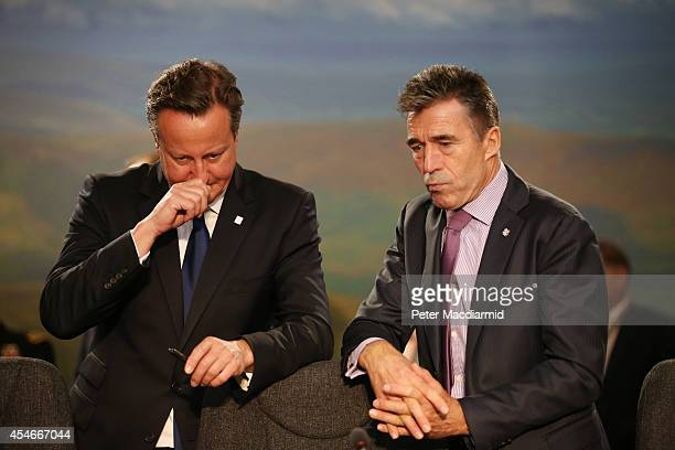 Secretary General Anders Fogh Rasmussen waits with British Prime Minister David Cameron at the start of the morning session at the NATO Summit on...