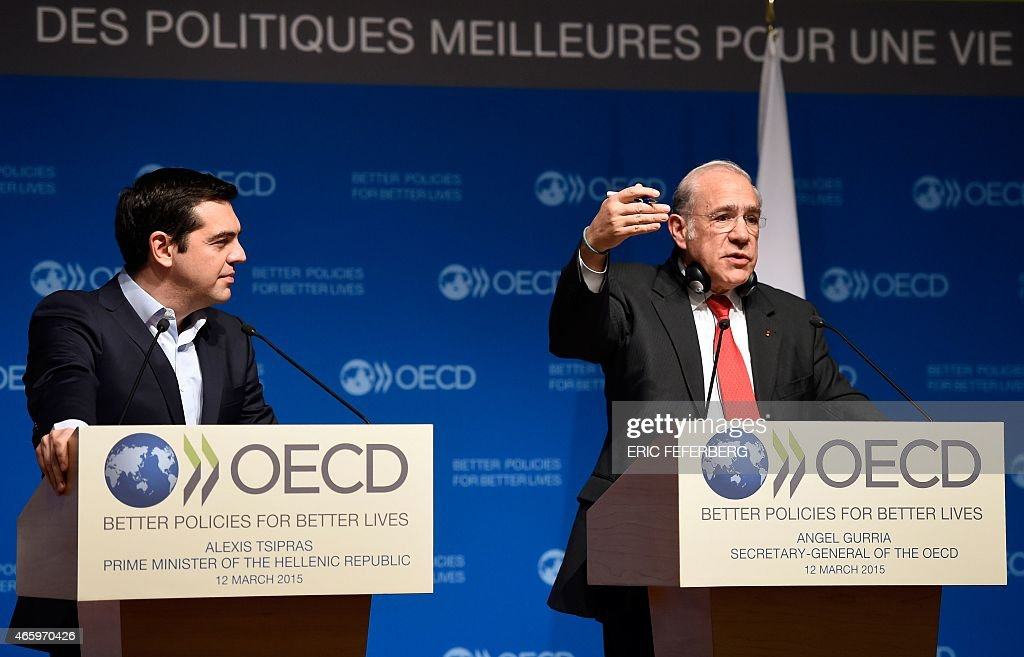 Secretary General Angel Gurria delivers a speech as Greek Prime Minister Alexis Tsipras looks on during Tsipras' visit to the OECD headquarters in...