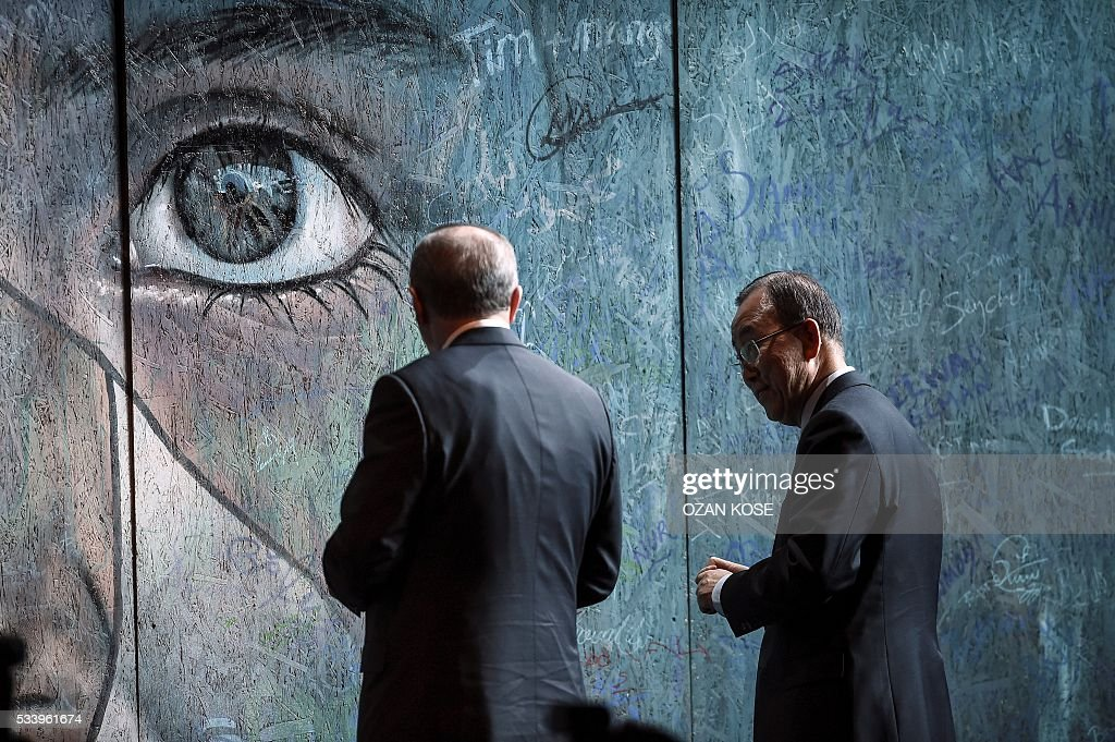 UN secretary general Ban Ki-moon (R) and Turkish President Recep Tayyip Erdogan (L) sign a graffiti wall during the closing cerenomy of the World Humanitarian Summit, on May 24, 2016 in Istanbul. UN Secretary General Ban Ki-moon on Tuesday said he was disappointed most top world leaders had stayed away from the first humanitarian summit in Istanbul, saying concrete political action was now needed. / AFP / OZAN