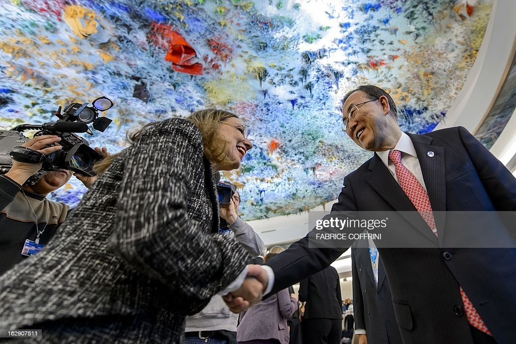 UN Secretary General Ban Ki-moon (R) shakes hands to an unidentified delegate beneath a ceiling painted by Spanish artist Miquel Barcelo, prior to Ban's address before the United Nations Human Rights Council on March 1, 2013 in Geneva.