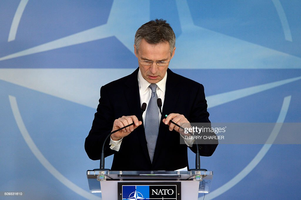 Secretary General Jens Stoltenberg adjusts the microphones as he talks to the media prior to a meeting of the North Atlantic Council (NAC) of Defence Ministers at the NATO headquarters in Brussels, February 10, 2016. NATO defence ministers begin two-day meeting to discuss issues including Turkey's request for help to deal with the migration crisis, the alliance's beefed up response to a more assertive Russia and the security threat posed by the Syria war. / AFP / THIERRY CHARLIER