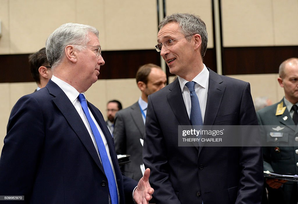 Secretary General Jens Stoltenberg (R) and British Defence Minister Michael Fallon (L) talk prior to a Global Coalition meeting held at the NATO headquarters in Brussels, February 11, 2016. / AFP / THIERRY CHARLIER