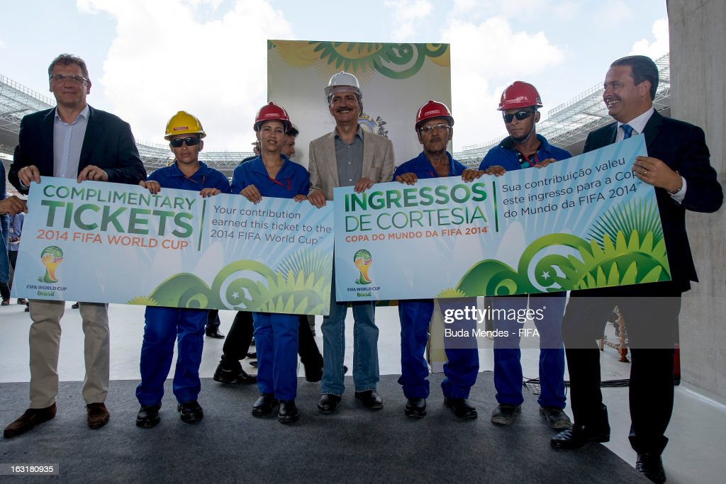 Secretary General Jerome Valcke (L), and Brazil's Sports Minister Aldo Rebelo (C) give a giant-size symbolic ticket to four construction workers involved in the construction of Arena Pernambuco Stadium during the 2014 FIFA World Cup Host City Tour on March 5, 2013 in Recife, Brazil.