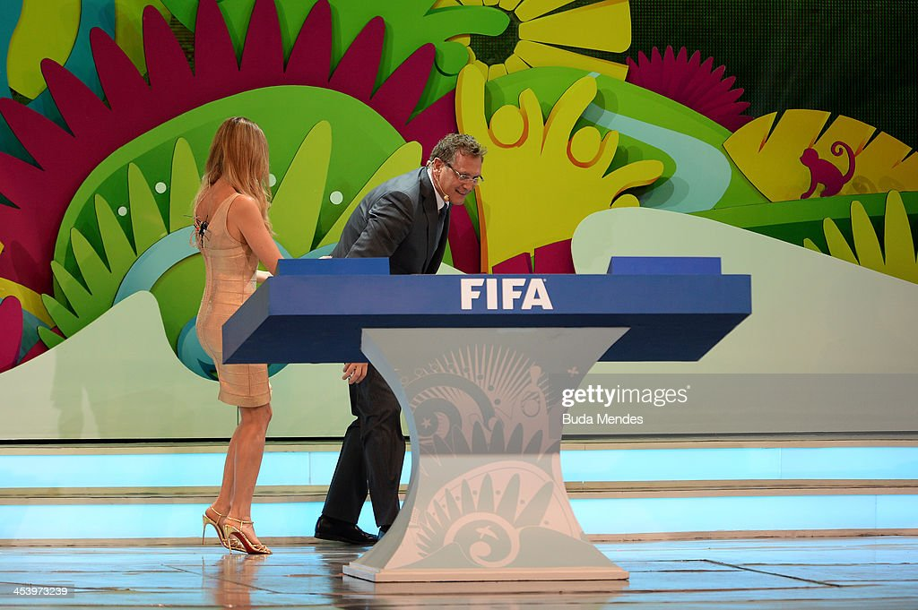 Secretary General Jerome Valcke collects one of the draw balls after was dropped on the floor next to host Fernanda Lima during the Final Draw for the 2014 FIFA World Cup Brazil at Costa do Sauipe Resort on December 6, 2013 in Costa do Sauipe, Bahia, Brazil.