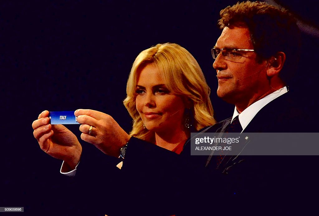 FIFA secretary general Jerome Valcke (not in picture), flanked by South African actress Charlize Theron holds up Italy during the World Cup 2010 draw at the Cape Town International Convention Centre (CTICC) in Cape Town on December 4, 2009. The draw itself sees the 32 teams divided into four pots of eight from which the eight groups that will contest the first round will be drawn.