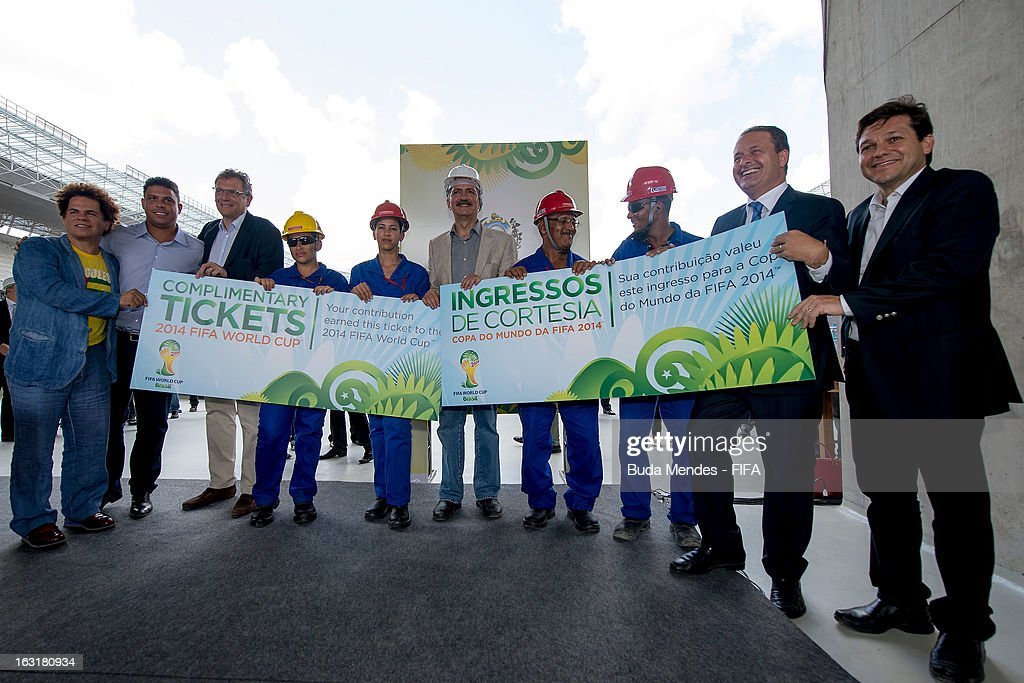 Secretary General Jerome Valcke (3L), (2L) Ronaldo Nazario, member of the Board of Administration of the Local Organising Committee (LOC), and Brazil's Sports Minister Aldo Rebelo (C) give a giant-size symbolic ticket to four construction workers involved in the construction of Arena Pernambuco Stadium during the 2014 FIFA World Cup Host City Tour on March 5, 2013 in Recife, Brazil.