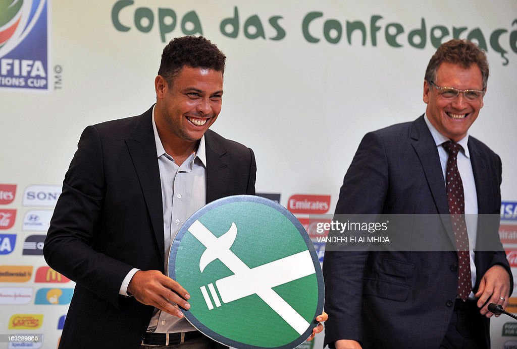 FIFA secretary general Jerome Valcke (R) smiles next to former footballer and member of the local Brazil 2014 FIFA World Cup Organizing Committee Ronaldo Nazario, after presenting a No Smoking sign, during a press conference on the Confederations Cup and WC2014, in Rio de Janeiro, Brazil, on March 7, 2013.