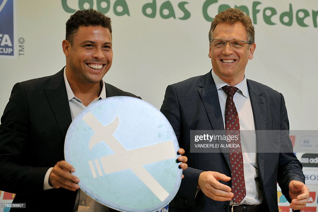 FIFA secretary general Jerome Valcke (R) smiles next to former footballer and member of the local Brazil 2014 FIFA World Cup Organizing Committee Ronaldo Nazario, after presenting a No Smoking sign, during a press conference on the Confederations Cup and WC2014, in Rio de Janeiro, Brazil, on March 7, 2013. AFP PHOTO/VANDERLEI ALMEIDA