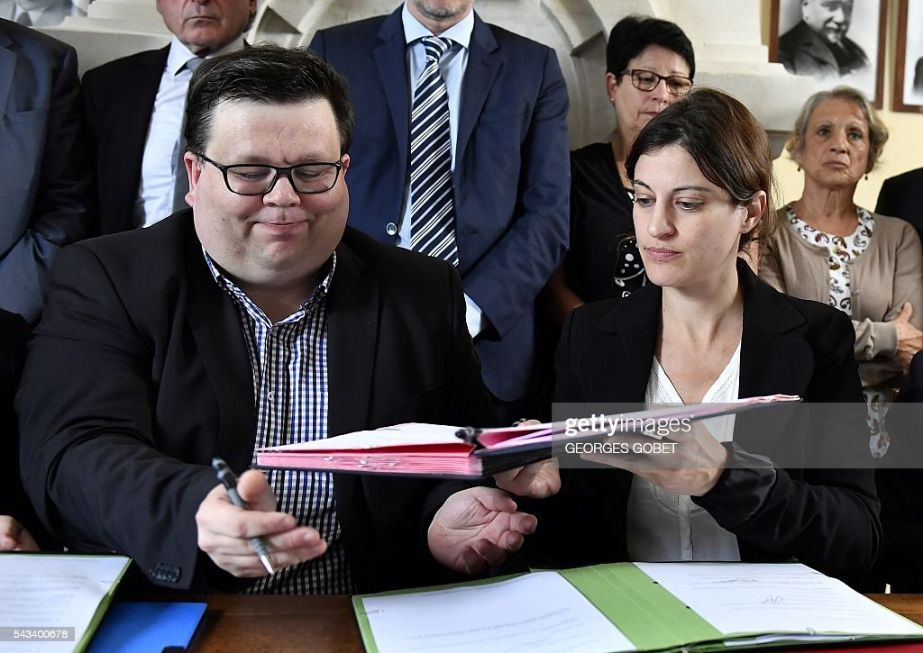 Secretary general of the Federation nationale des victimes d'attentats et d'accidents collectifs (Fenvac - National Federation of Victims of Bombings and Mass Accidents) Stephane Gicquel (L) and French Junior Minister for Victims Aid Juliette Meadel (R) sign on June 28, 2016 in Puisseguin an amicable agreement on the compensation for relatives of the victims of the road accident where a coach carrying elderly day-trippers collided with a lorry that killed 43 people on October 23, 2015 near the village of Puisseguin. The majority of the beneficiaries of the 43 killed persons during the accident, will receive a compensation of 11 millions euros from the insurances, announced their lawyers on June 28, 2016. / AFP / GEORGES