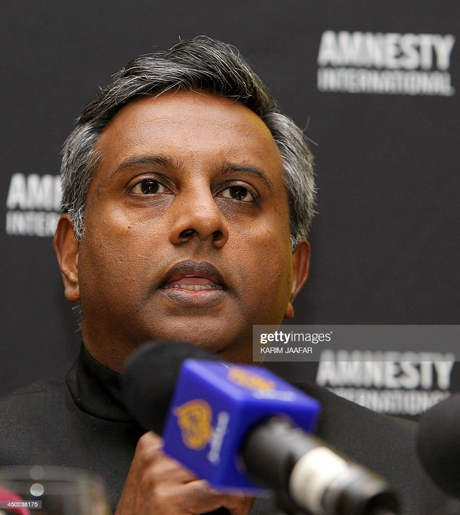 Secretary General of the human rights organization Amnesty International Salil Shetty displays a report during a press conference in Doha on November 17, 2013. Amnesty International urged Qatar to end abuse of migrants working on football World Cup infrastructure, as it issued its report citing cases in which they were referred to as 'animals'. OUT ==