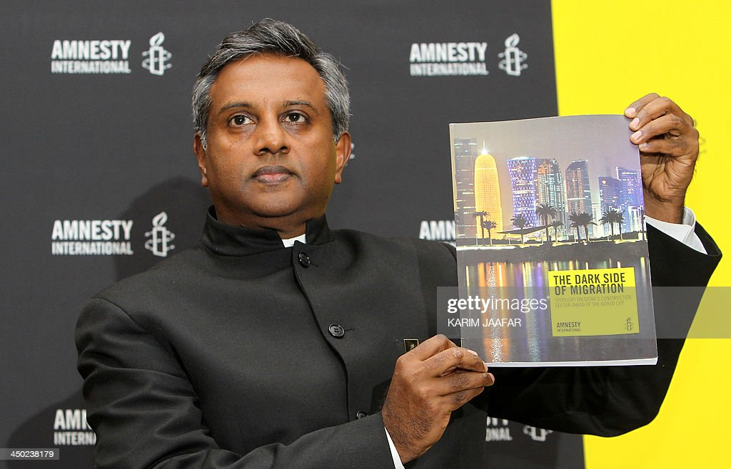 Secretary General of the human rights organization Amnesty International Salil Shetty displays a report during a press conference in Doha on November 17, 2013. Amnesty International urged Qatar to end abuse of migrants working on football World Cup infrastructure, as it issued its report citing cases in which they were referred to as 'animals'.