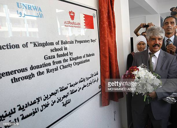 Secretary General of the Royal Charity Organization in the Kingdom of Bahrain Mustafa alSayed holds a flower bouquet as he opens a UNRWA school...