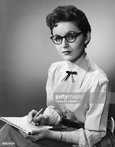 A secretary in hornrimmed glasses gets ready to take dictation 1955