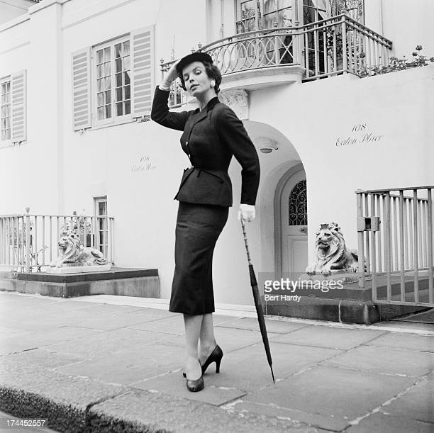 Secretary Janet Jones undergoing training for a career in modelling wearing a fitted suit with belted waist and pencil skirt outside a house in Eaton...
