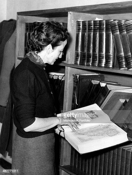 A secretary observing a map in front of a bookcase 1950s