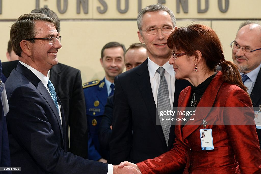 US Secretary of Defence Ashton Carter (L) and Slovenia's Defence Minister Andreja Katic (R) shake hands beside Nato Secretary General Jens Stoltenberg (C) prior to a meeting of the North Atlantic Council (NAC) of Defence Ministers at the NATO headquarters in Brussels, February 10, 2016. NATO defence ministers convene a two-day meeting to discuss current defense issues and whether the Alliance should take a more direct role in dealing with its gravest migrant crisis since Worl War II. / AFP / THIERRY CHARLIER