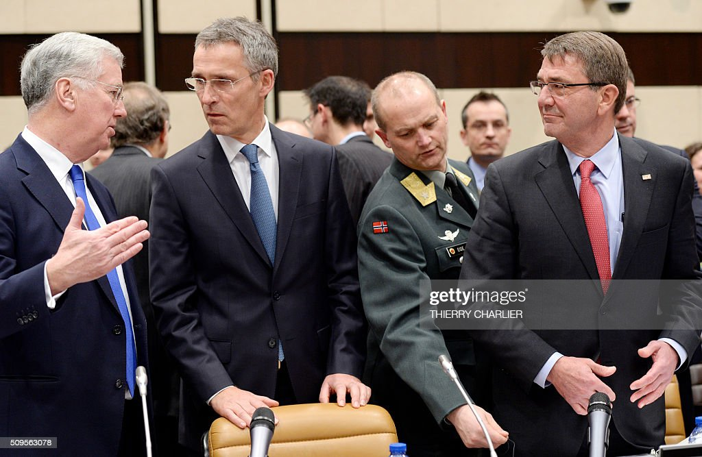 US Secretary of Defence Ashton Carter (R) NATO Secretary General Jens Stoltenberg, (C) and British Defence Minister Michael Fallon (L) talk prior to a Global Coalition meeting held at the NATO headquarters in Brussels, February 11, 2016. / AFP / THIERRY CHARLIER
