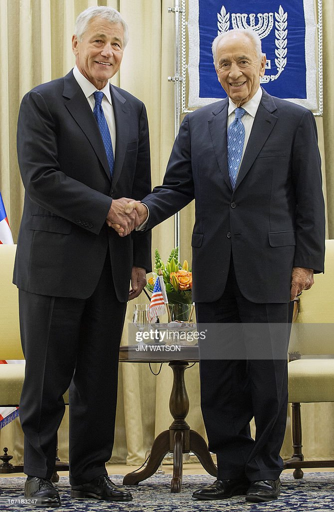 US Secretary of Defence Chuck Hagel (L) shakes hands with Israeli President Shimon Peres at the President's office in Jerusalem on April 22, 2013. Hagel arrived in Israel at the start of a six-day regional tour, his first since taking over as Pentagon chief two months ago, which was likely to be dominated by concerns over Iran's nuclear programme and Syria's civil war. AFP PHOTO/POOL/JIM WATSON
