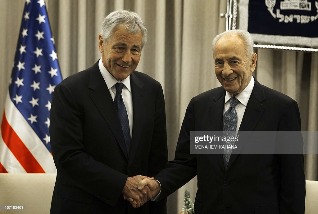 US Secretary of Defence Chuck Hagel (L) shakes hands with Israeli President Shimon Peres at the President's office in Jerusalem on April 22, 2013. Hagel arrived in Israel at the start of a six-day regional tour, his first since taking over as Pentagon chief two months ago, which was likely to be dominated by concerns over Iran's nuclear programme and Syria's civil war. AFP PHOTO/POOL/MENAHEM KAHANA
