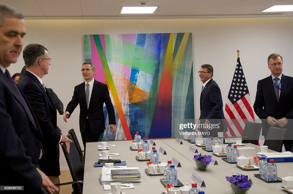 U.S. Secretary of Defense Ash Carter (2nd R) greets members at the table along with NATO Secretary General Jens Stoltenberg (3rd L) during a meeting at NATO headquarters in Brussels on February 10, 2016. NATO defense ministers convene a two-day meeting to discuss current defense issues and whether the Alliance should take a more direct role in dealing with its gravest migrant crisis since WWII. / AFP / POOL / Virginia Mayo