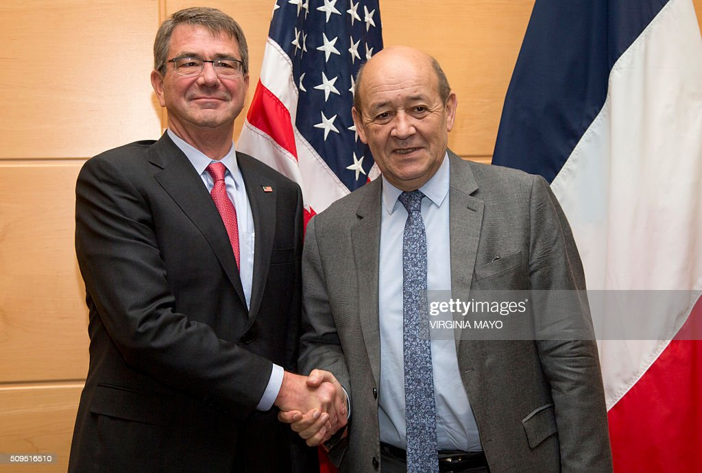 U.S. Secretary of Defense Ash Carter (L) shakes hands with French Defense Minister Jean-Yves Le Drian prior to a meeting at NATO headquarters in Brussels on February 11, 2016. NATO defense ministers met for a second day on Thursday to discuss Turkeys request to help deal with Europes ongoing migrant crisis and the current situation in Iraq and Syria. / AFP / POOL / Virginia Mayo
