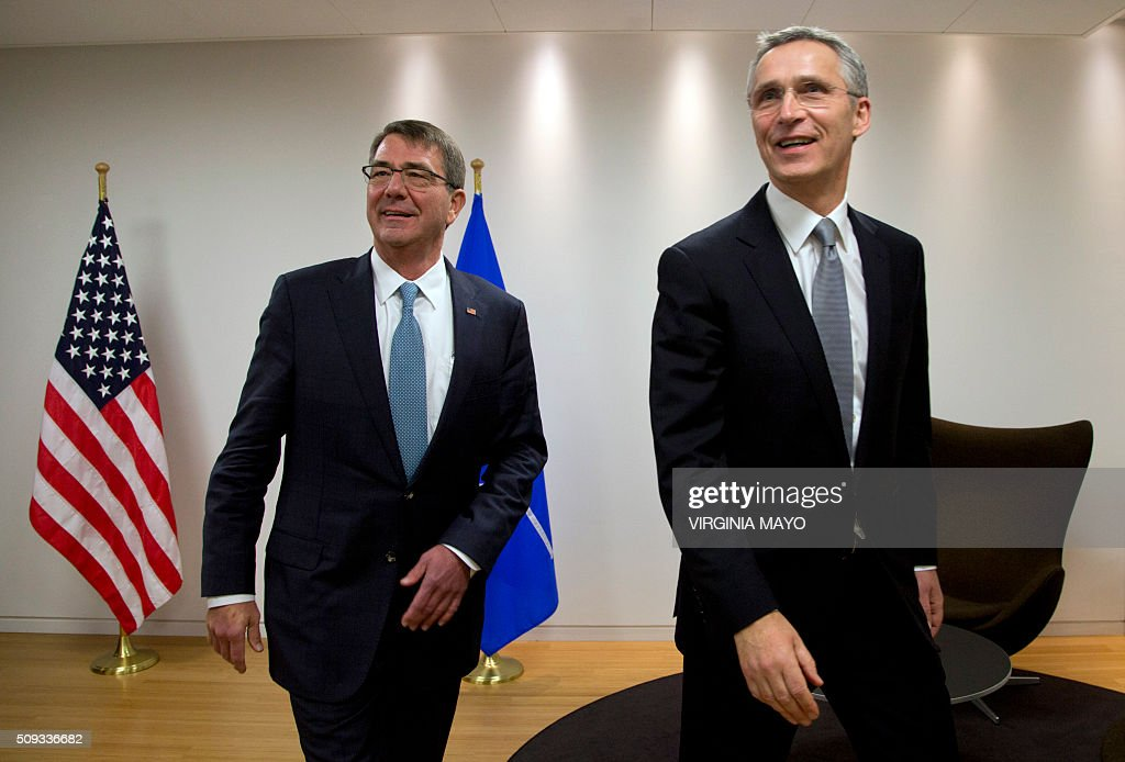 U.S. Secretary of Defense Ash Carter (L) walks with NATO Secretary General Jens Stoltenberg prior to a meeting at NATO headquarters in Brussels on February 10, 2016. NATO defense ministers convene a two-day meeting to discuss current defense issues and whether the Alliance should take a more direct role in dealing with its gravest migrant crisis since WWII. / AFP / POOL / Virginia Mayo