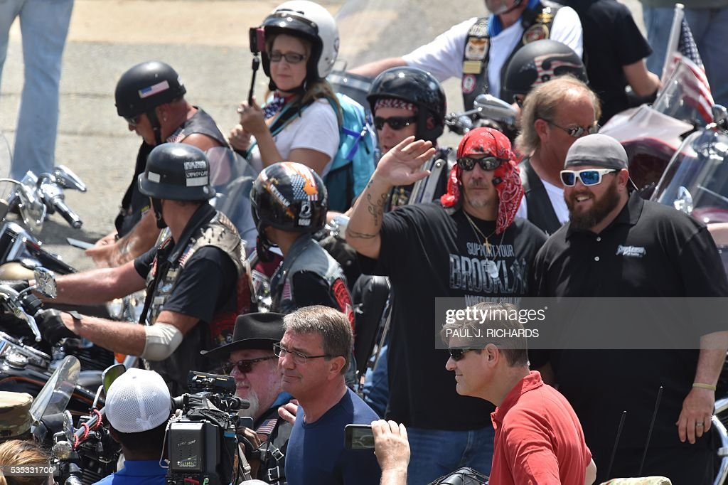 US Secretary of Defense Ashton Carter(bottom-center in blue shirt) is seen with motorcyclists participating in the Rolling Thunder XXIX Ride For Freedom in the Pentagon parking lot May 29, 2016 shortly before parading through Washington, DC, to raise awareness for American Prisoners of War and warriors currently missing in action. / AFP / PAUL