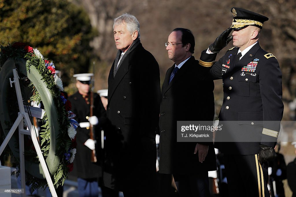 U.S. Secretary of Defense <a gi-track='captionPersonalityLinkClicked' href=/galleries/search?phrase=Chuck+Hagel&family=editorial&specificpeople=504963 ng-click='$event.stopPropagation()'>Chuck Hagel</a>, from left, French President Francois Hollande, and Maj. Gen. Jeffrey S. Buchanan, commander of the U.S. Army Military District of Washington, stand at attention after laying a wreath at the Tomb of the Unknown Soldier as 'Taps' is played at Arlington National Cemetery on February 11, 2014 in Arlington, Virginia. 2014 marks the 70th anniversary of the Allied Forces D-Day landing in Normandy, which helped lead to the liberation of France and the European continent.