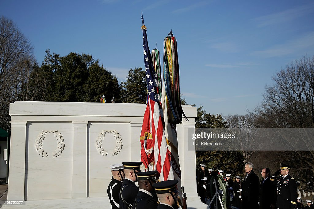 U.S. Secretary of Defense Chuck Hagel, from left, French President Francois Hollande, and Maj. Gen. Jeffrey S. Buchanan, commander of the U.S. Army Military District of Washington, stand at attention after laying a wreath at the Tomb of the Unknown Soldier as 'Taps' is played at Arlington National Cemetery on February 11, 2014 in Arlington, Virginia. 2014 marks the 70th anniversary of the Allied Forces D-Day landing in Normandy, which helped lead to the liberation of France and the European continent.