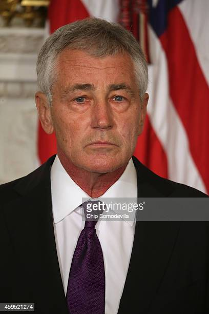 Secretary of Defense Chuck Hagel listens to President Barack Obama highlight his accomplishments during the announcement of Hagel's resignation in...