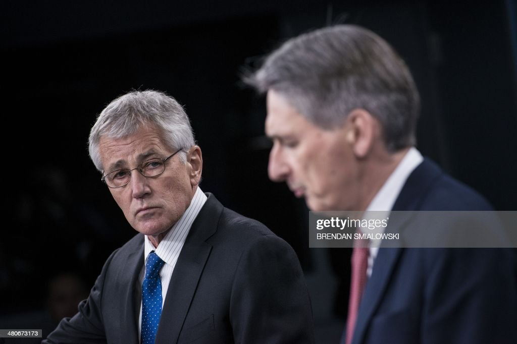 US Secretary of Defense Chuck Hagel (L) listens while British Defense Secretary Philip Hammond speaks during a press conference at the Pentagon on March 26, 2014 in Washington, DC. Hagel and Hammond held the briefing after a bilateral meeting earlier at the Pentagon where they spoke about the Ukraine and other issues. AFP PHOTO/Brendan SMIALOWSKI