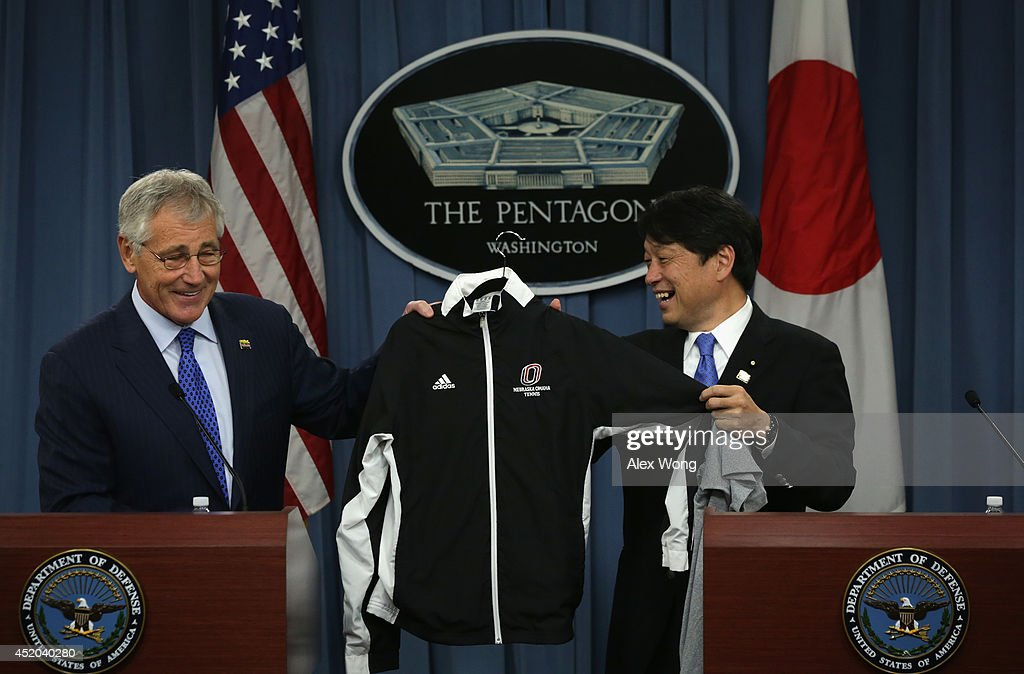 U.S. Secretary of Defense Chuck Hagel (L) presents Japanese Minister of Defense Itsunori Onodera (R) with a tennis outfit from the University of Nebraska Omaha, Hagel's alma mater, during a joint news conference at the Pentagon July 11, 2014 in Arlington, Virginia. Onodera is on an eight-day visit in the U.S.