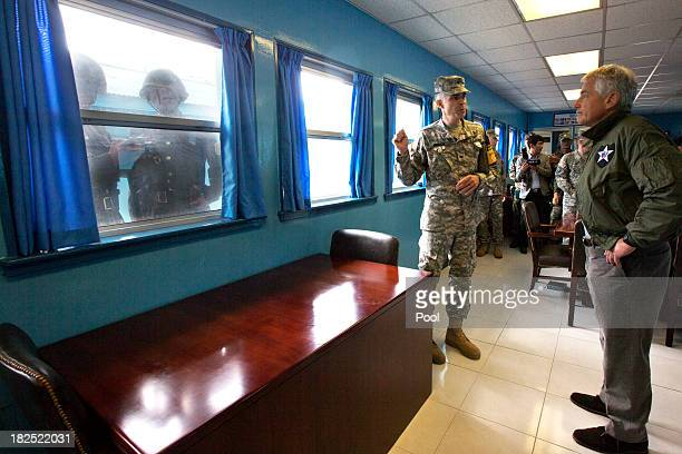 S Secretary of Defense Chuck Hagel right listens to US Army Col James Minnich as North Korean soldiers photograph through a window at a UN truce...