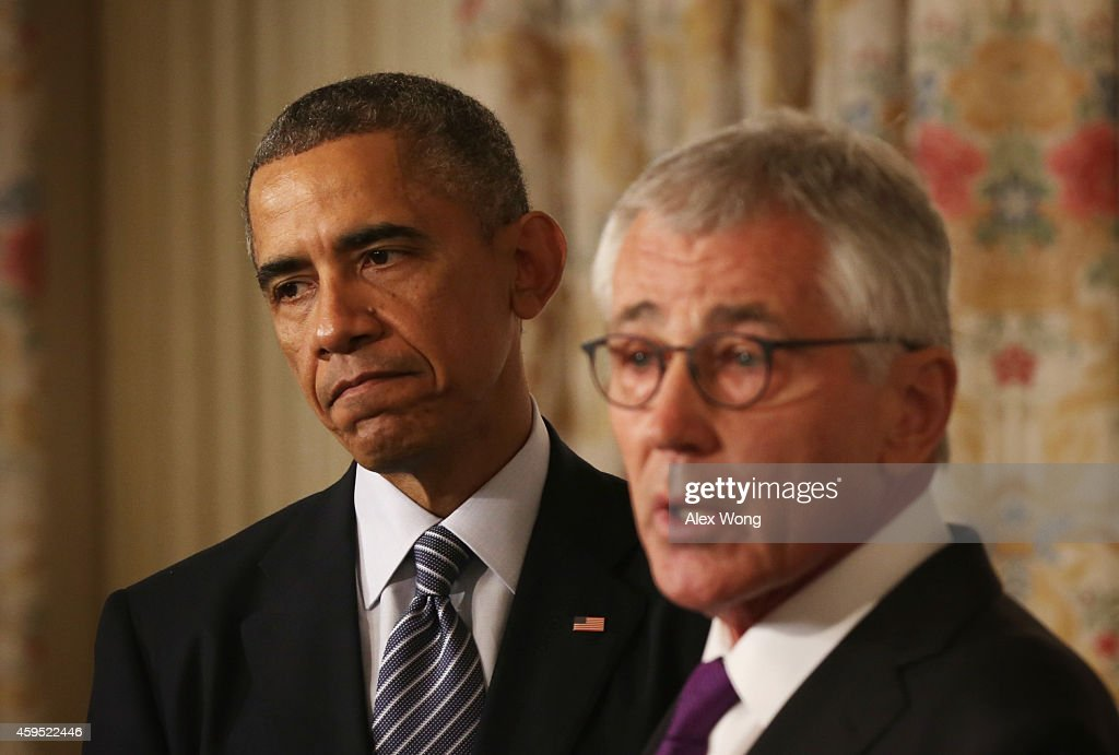U.S. Secretary of Defense <a gi-track='captionPersonalityLinkClicked' href=/galleries/search?phrase=Chuck+Hagel&family=editorial&specificpeople=504963 ng-click='$event.stopPropagation()'>Chuck Hagel</a> (R) speaks as President <a gi-track='captionPersonalityLinkClicked' href=/galleries/search?phrase=Barack+Obama&family=editorial&specificpeople=203260 ng-click='$event.stopPropagation()'>Barack Obama</a> (L) listens during a press conference announcing Hagel's resignation in the State Dining Room of the White House November 24, 2014 in Washington, DC. Sources say Hagel plans to remain in office until his successor is confirmed by the Senate.